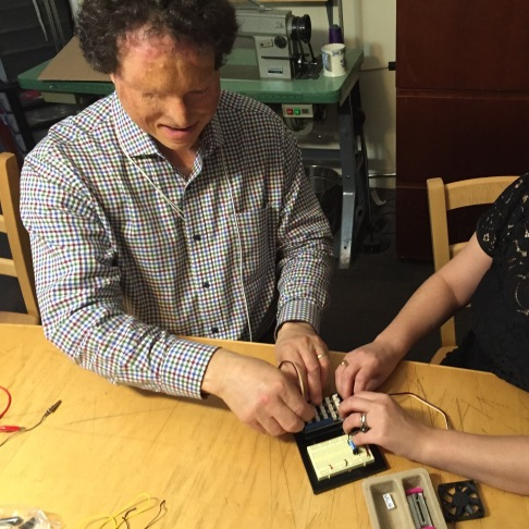 Man with visual impairment works with a woman to use Arduino