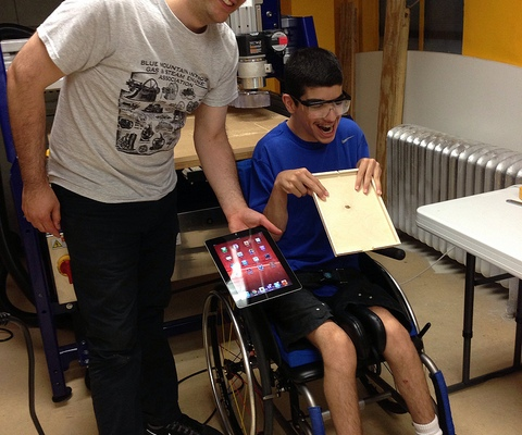 Two men in a workshop, one seated in a wheelchair smiling with a custom-made iPad case, the other stands smiling with the iPad.