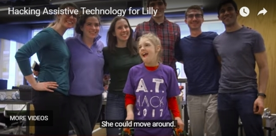 "YouTube player screen shot shows young girl wearing AT Hack 2017 t-shirt, standing with walker device, surrounded by smiling college students. Caption says ""she could move around."" Video title is Hacking Assistive Technology for Lilly."