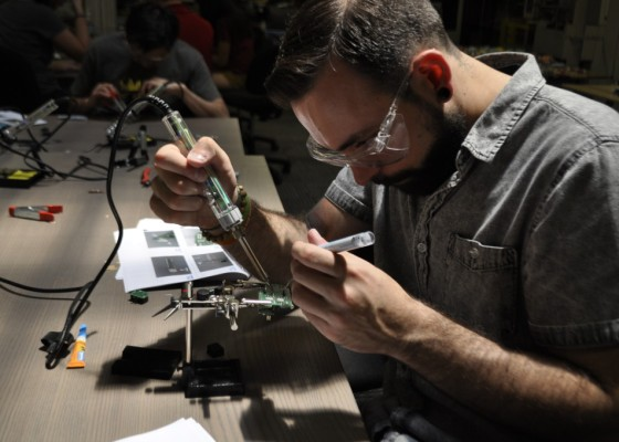 Man wearing protective eye-wear works with tools intently.