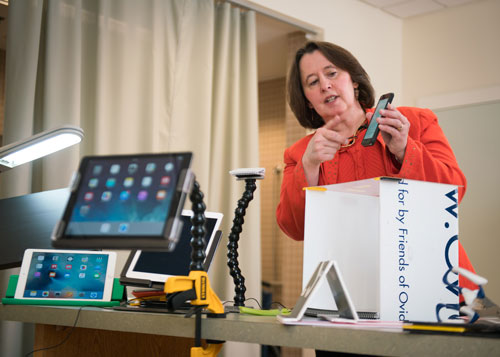 A woman behind a table that displays tablets mounted in different ways, including Loc-Line with a clamp, holds and points to a smart phone.