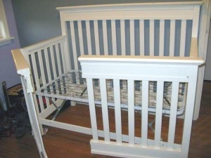 A crib frame with the front side divided in half like swinging French doors