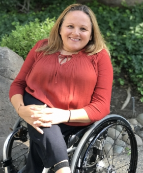 A woman with dwarfism smiling and seated in a wheelchair outdoors