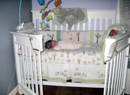 The crib with the front swung open and a baby asleep inside.