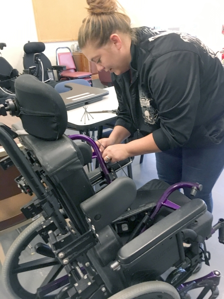 A woman works on a pediatric wheelchair in a room of equipment