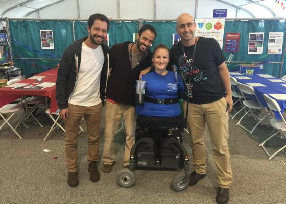 A woman in a power chair, who has no arms or legs, smiling, flanked by three men who are standing and smiling. They are in an exhibition tent.