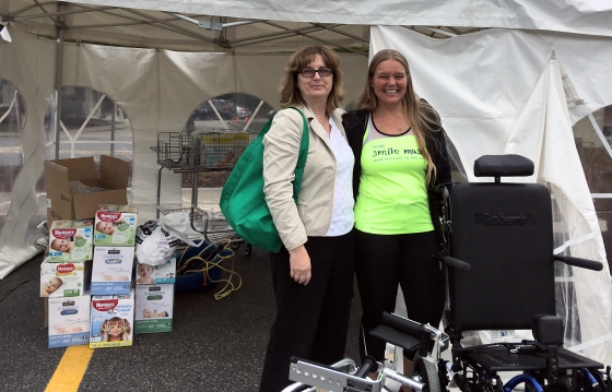 Two women smiling in front of a tent with boxes of adult diapers and next to wheelchairs.