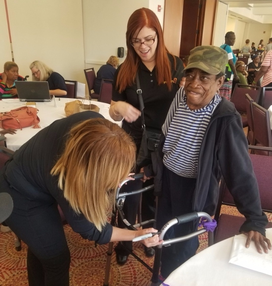 A woman Caribbean hurricane refugee with a walker receiving equipment assistance from two women in a conference center room.