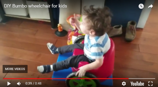 Screenshot of YouTube video titled: DIY Bumbo wheelchair for kids. Shows a toddler giving the thumbs up while seated in his homemade Bumbo wheelchair.