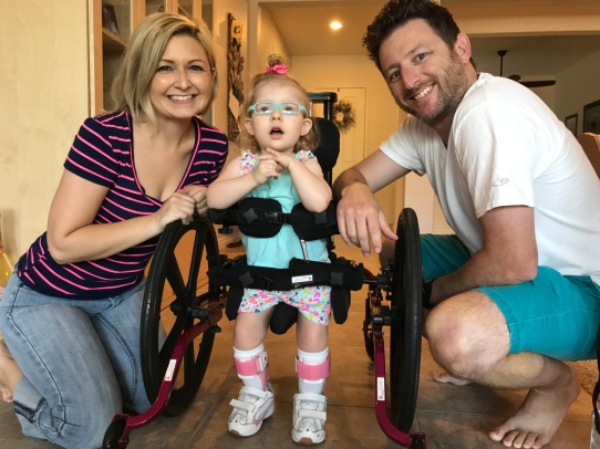 A little girl standing supported by a wheeled gait-trainer device for walking and flanked by her smiling parents.