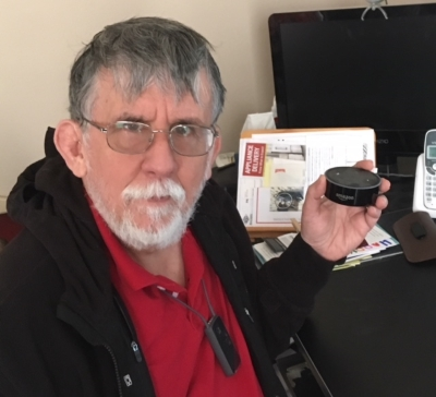 A man seated at a desk holding an Echo Dot device.