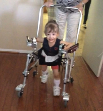 A smiling little girl using a pediatric walker with forearm supports and hip guide. There's an adult guiding from behind.
