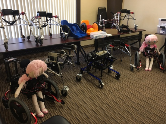 A room full of equipment, mostly walkers and gait trainers. Two support child-size dolls.