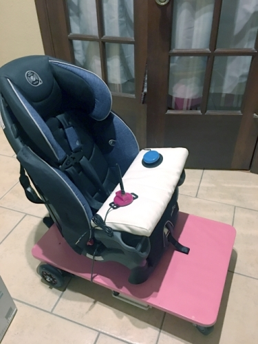 A scooter made of a car seat mounted to a motorized platform. There's a tray with a joystick and a big mac type switch mounted to the car seat.