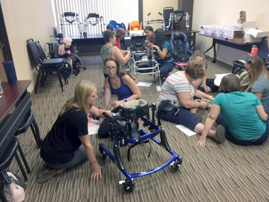 Women working in groups on the floor with pediatric mobility equipment.
