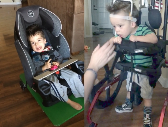 Two boys using specialized pediatric mobility devices. One is seated in a car seat on a wheeled platform controlled by a joystick, the other is standing in a walker with torso support and a head pod.