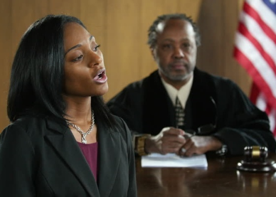 An attorney speaking in court with a judge listening seated in the background.