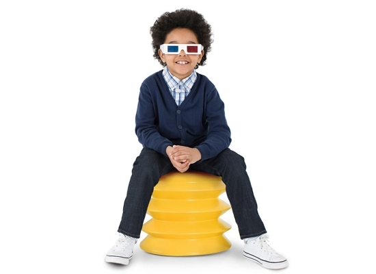 Cute smiling boy wearing 3D paper glasses seated on ergoergo stool which is a plug shape with accordion folds in yellow plastic.