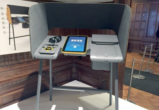 Accessible voting booth with headphones and tablet computer display as well as tactile input module. Booth and devices have rounded co