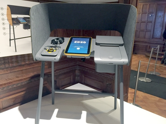 Wheelchair-accessible voting booth with headphones and tablet computer display.