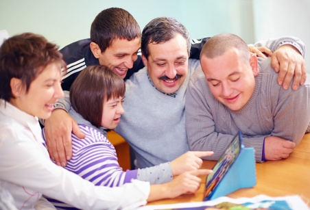 A family of five smiling and clustered over a tablet computer. The daughter has a developmental disability and is pointing at the screen with her mother.
