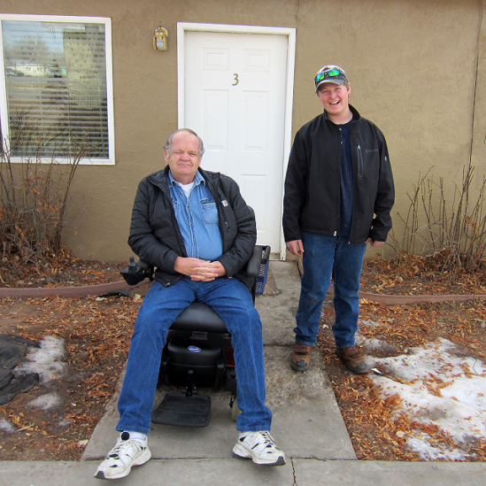 A man seated in a power wheelchair smiles next to a smiling teenager standing outside the door to a house.