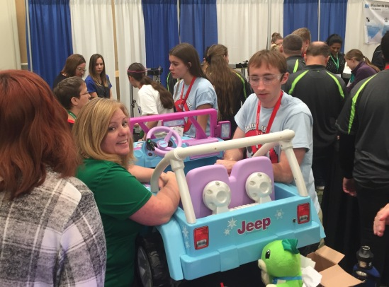 A young man and woman working on a toy Jeep in a busy exhibit hall.