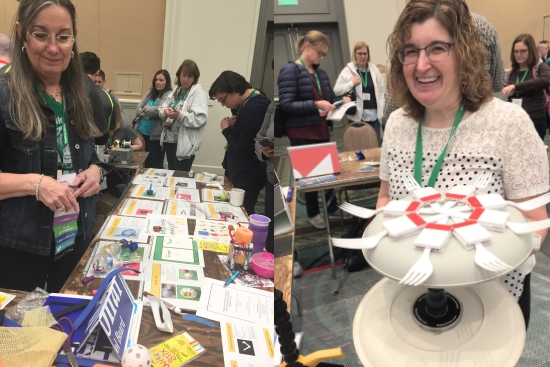 Two smiling women with their materials in a busy exhibit hall. Schoonover overlooks a table of printed instructions and materials for making art. Driscoll holds a rotating elevated plate equipped with forks pointing outward like spokes.
