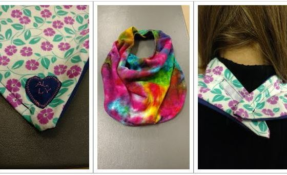 Three images. 1) close-up of the corner of a garment protector shows a heart with initials embroidered. 2) a tie-dye styled adult bib. 3) close-up of how a garment protector fastens on the back of the neck with velcro.