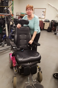 A woman in a warehouse leans over a power wheelchair.