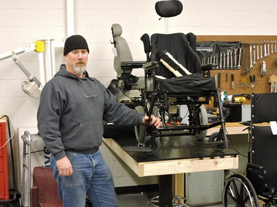 A man wearing jeans and a knit cap stands next to a work bench holding two wheelchairs. Tools are mounted on the wall behind.