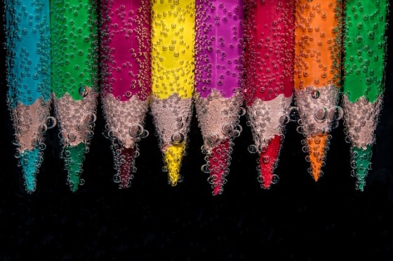 A rainbow of colored pencil tips underwater