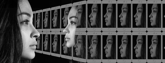 Profile of a young woman looking at her reflection which is superimposed over two rows of iPhones displaying the same profile of her face.