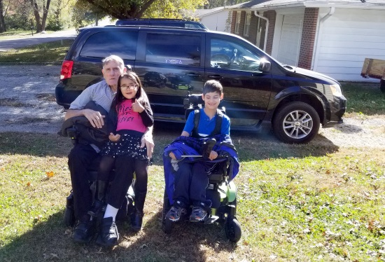 An older man in a powerchair with a young girl on his lap and a boy in his powerchair beside him. They are outside with a van in the background.
