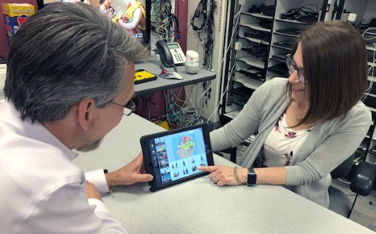 A man and a woman looking at an iPad with an AAC display. In the background are shelves with electronics equipment.