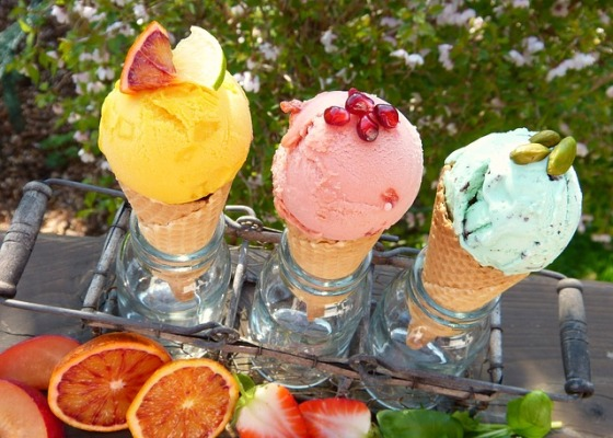 Three ice cream cones held upright in Ball Jars supported by an antique jar-holding tray. They are outside on a wooden table with cut fruit in front and flowers in the background.