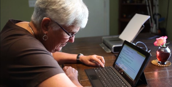An older woman using a tablet computer with keyboard at her desk. Behind her is a portable printer with paper.