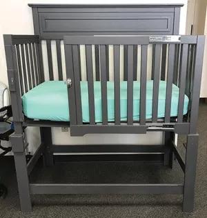A crib with a sliding gate.