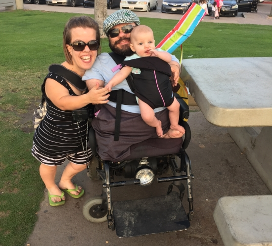 Two parents and a baby smiling for a picture. The mom stands embracing dad in his wheelchair. He is wearing baby in a front carrier. Both parents have dwarfism.