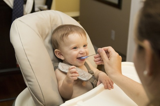 Smiling baby in high chair being fed with a spoon
