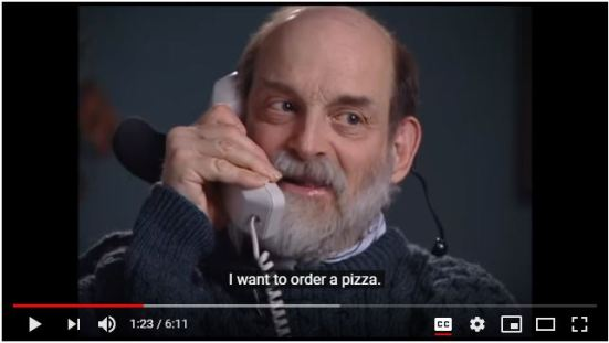 Screenshot of a YouTube video shows an older man speaking into a telephone handset with the caption