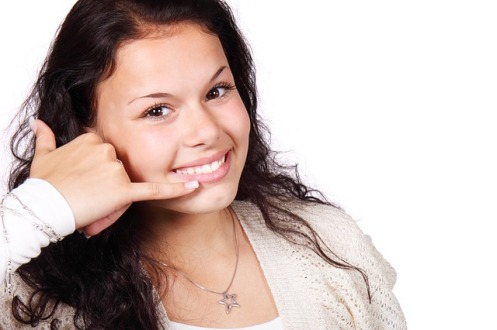 A young woman smiling and holder her hand to her face with pinky and thumb spread in a telephone handset gesture.