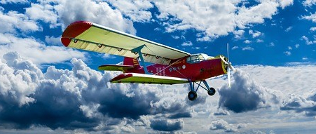 A retro prop plane flying among clouds and a blue sky.