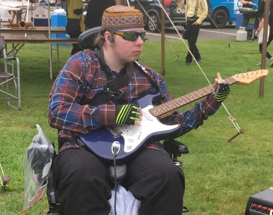 A young man playing an electric guitar seated in a power wheelchair. He is outside and wearing sunglasses and a headset.