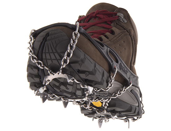 A hiking boot with metal crampon spikes stretched across the sole.