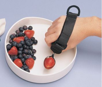 A hand wearing a velcro-style cuff that holds a spoon with a strawberry. There is a loop at the back of the hand. The hand is scooping from a wide-brimmed bowl containing blueberries and strawberries.