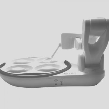 A sleek robotic device featuring four rotating bowls and a spoon mounted to a mechanical arm.