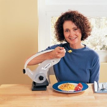 A woman seated eating with a fork with her arm supported in a large mounted loop-shaped bracket device that is hinged and swivels.