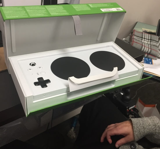 The Xbox Adaptive Controller in its packaging, lid lifted, showing loops to lift to remove the product and open the lid.