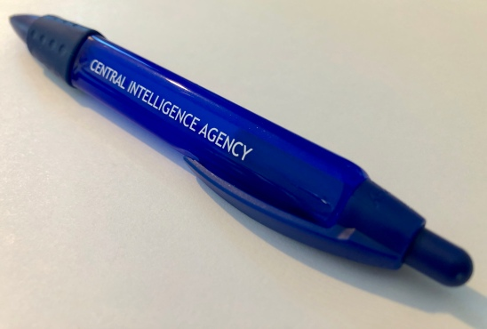 A plastic button-top retractable pen with the words Central Intelligence Agency on one of its three sides. Has rubber grip band and a clip.